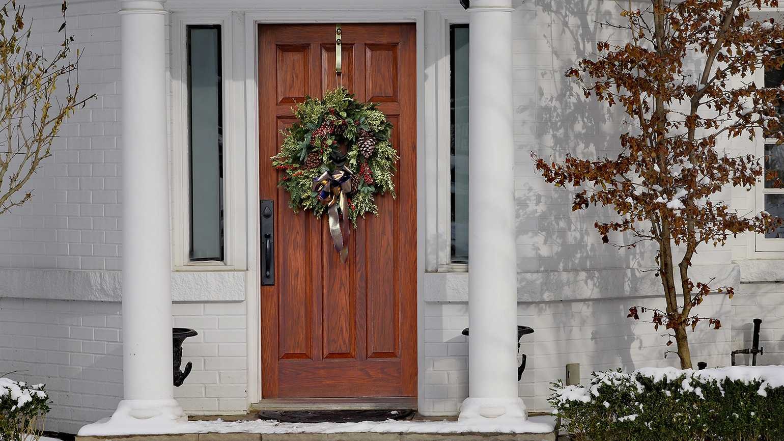 A Christmas wreath on the door of a white house