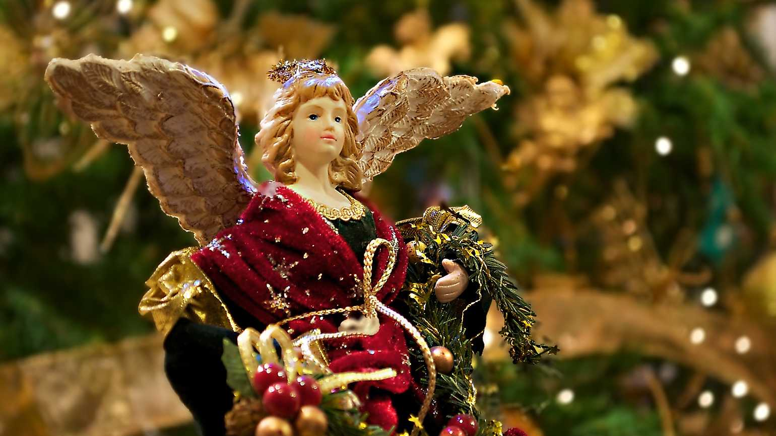 An ornament of an angel in a Christmas tree wearing festive holiday robes