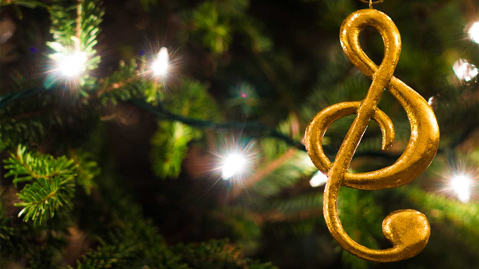 Golden music symbol ornament hanging from well-lit Christmas tree