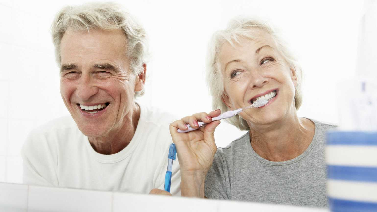 An older couple brushing their teeth together.