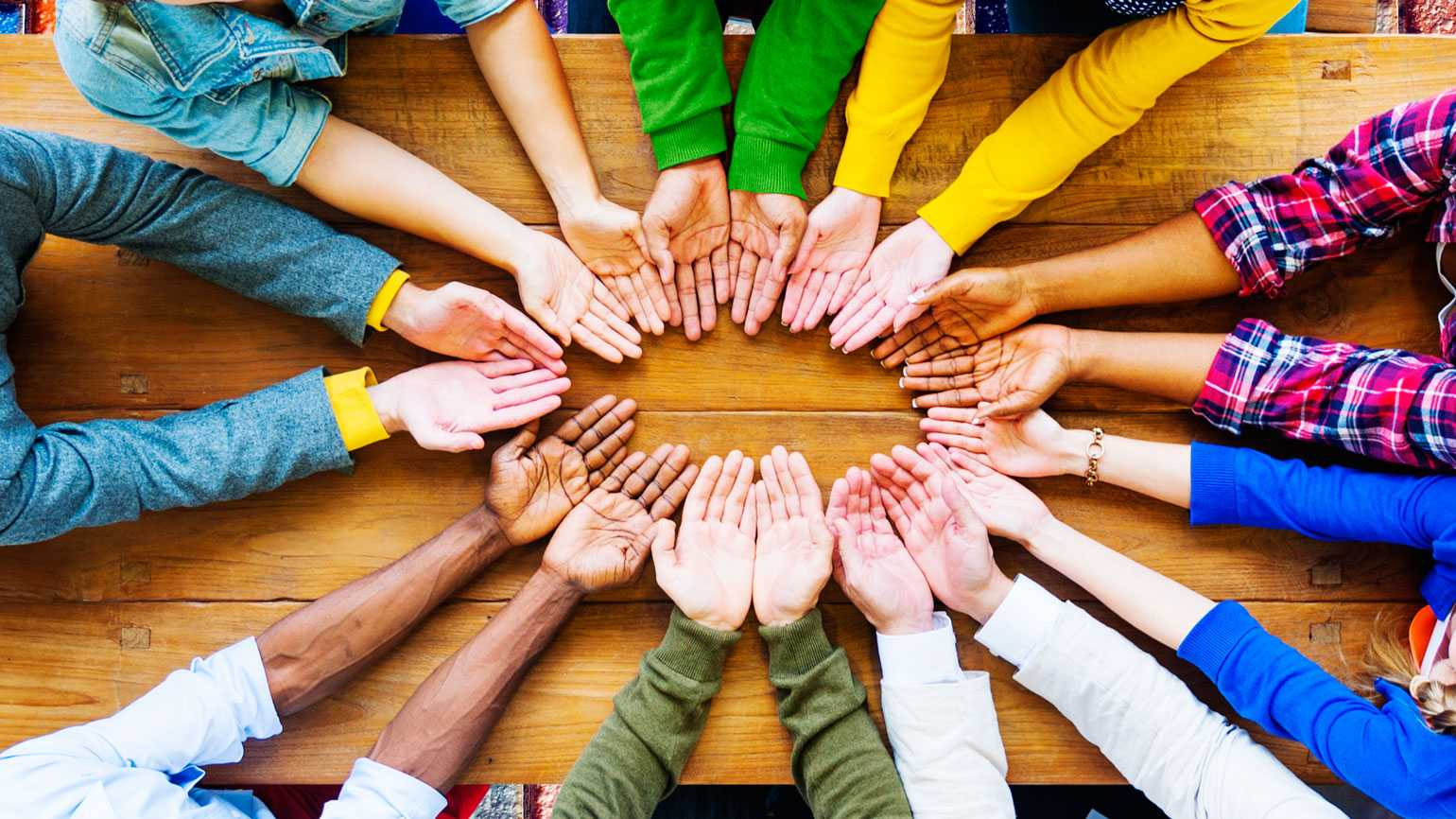 A circle of hands of people of different cultures displays a spirit of generosity