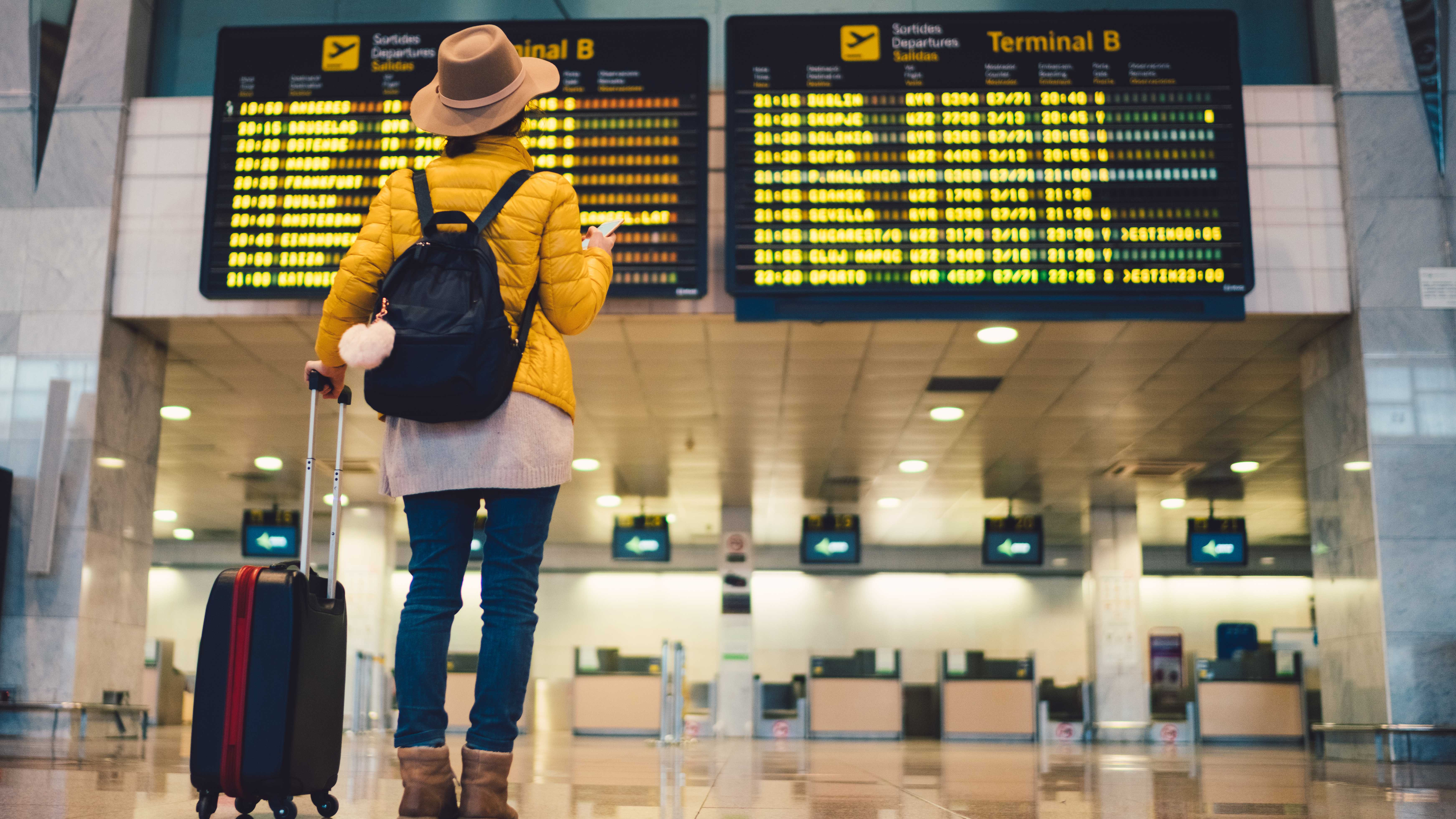 Woman looking at departure board in airport