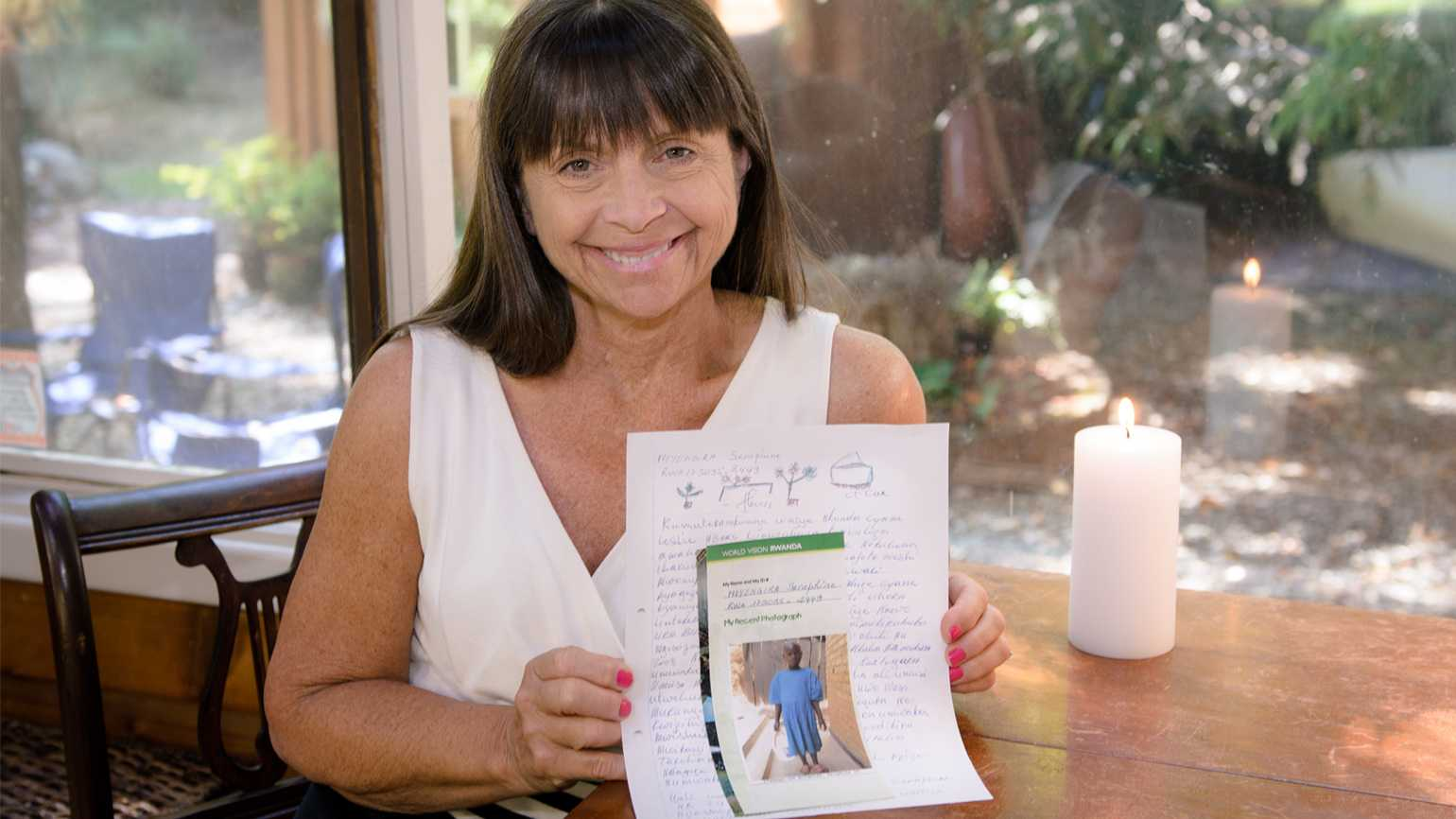 Leslie Kelly holds a letter she received from her sponsored child, Seraphine.