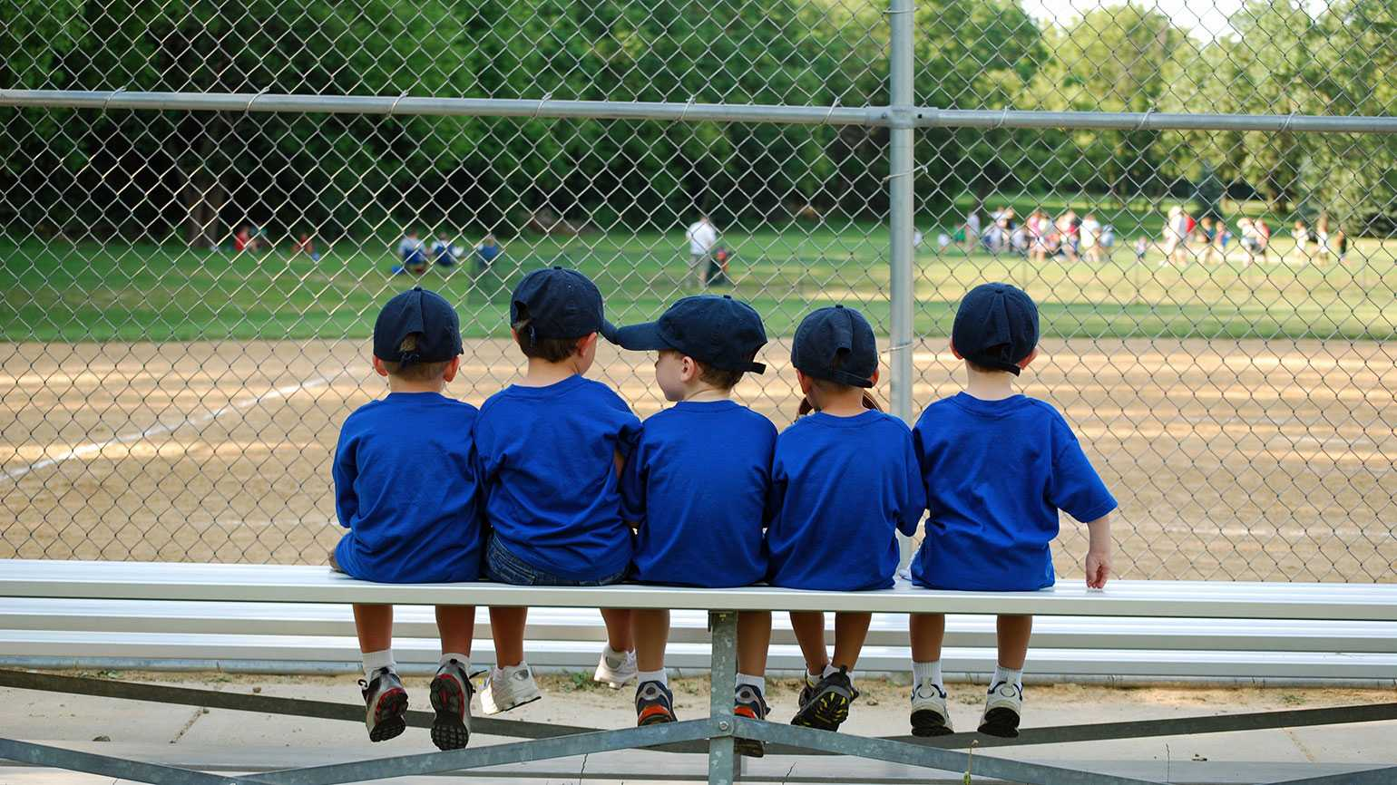 A quintet of Little Leaguers watch the action on the field