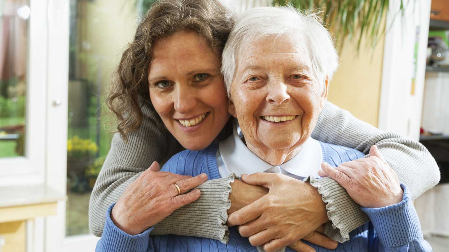 A woman and her aging mother in a loving embrace.