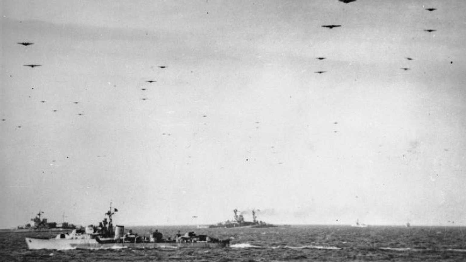 The Royal Navy during the Second World War- Operation Overlord (the Normandy Landings)- D-day 6 June 1944 Glider borne troops passing over units of the Royal Navy on their way to the invasion beaches of Normandy. In the background are the battleships HMS