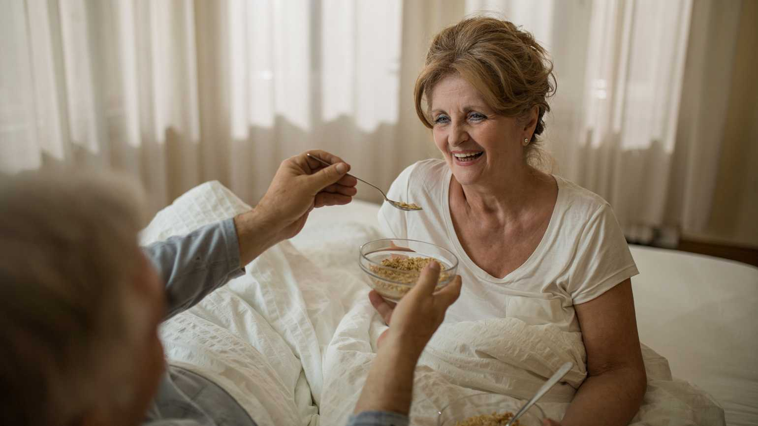 A woman being fed oatmeal in her bed.
