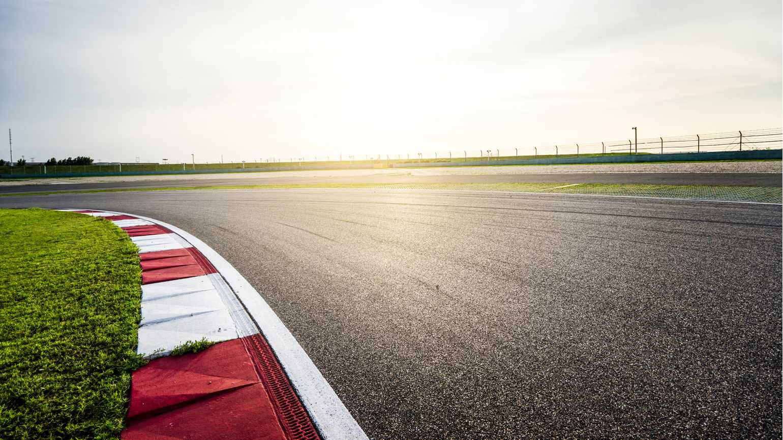 A close up on a car race track as brilliant sunlight pours through.