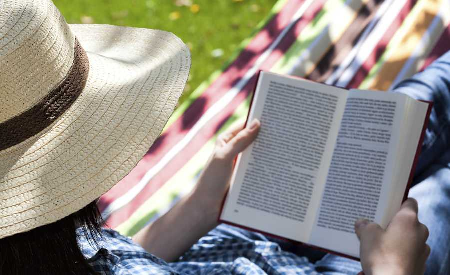 Guideposts: A man wearing a straw hat reads a book in a hammock on a summer afternoon.