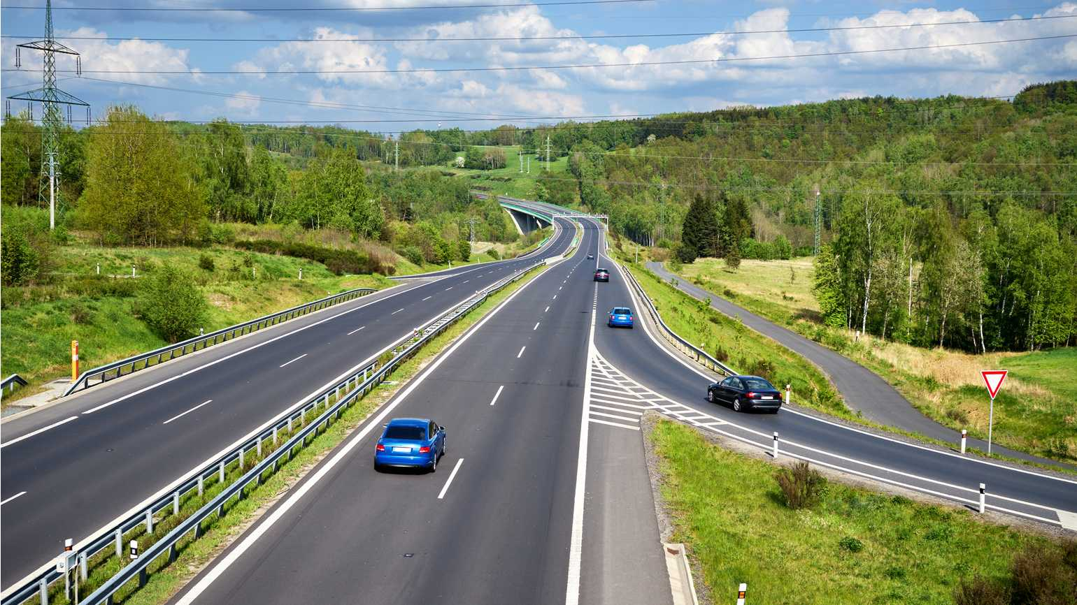 Various cars entering a highway lined with lush forests.