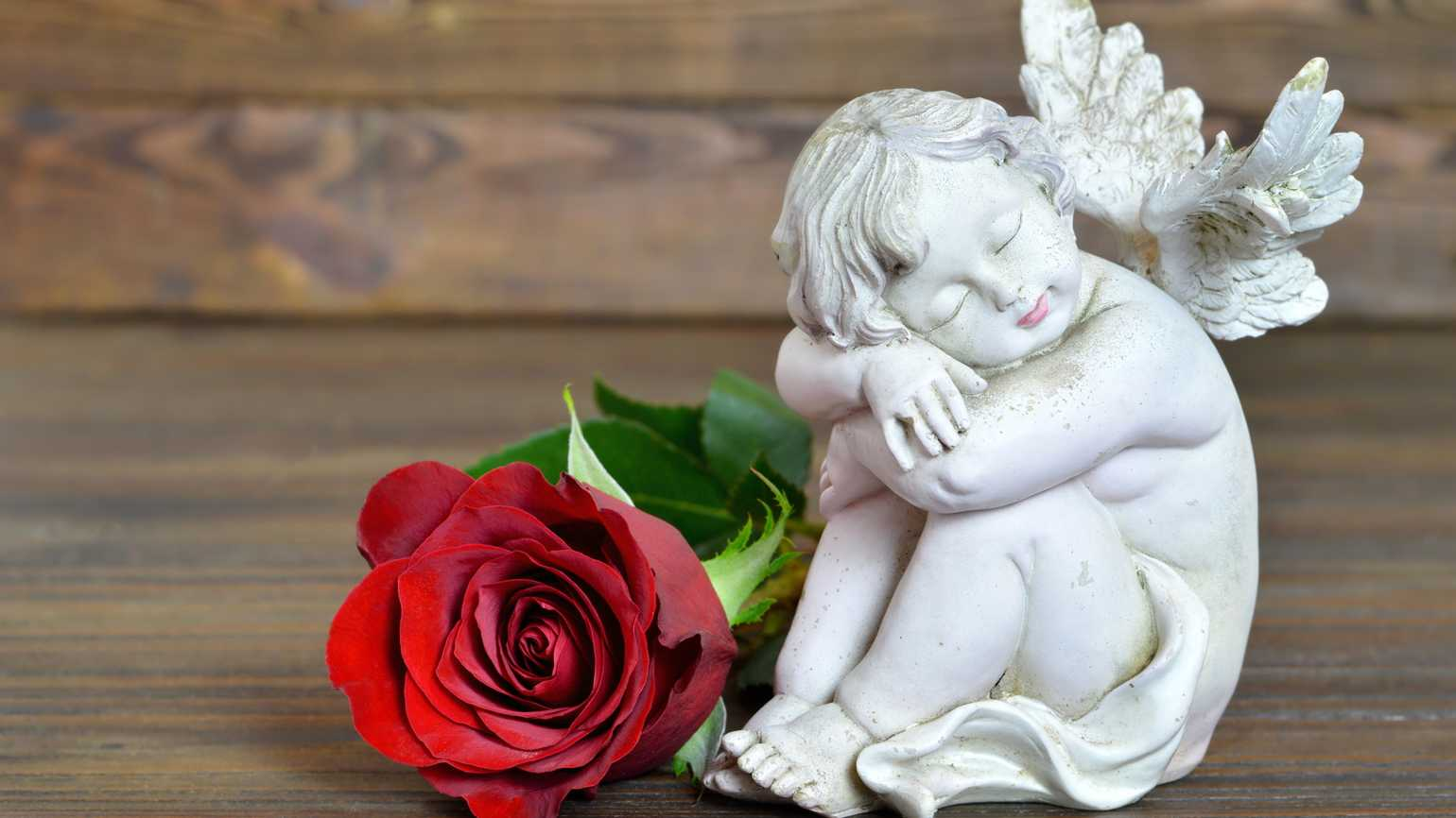 A small figurine of an angel next to a red rose.