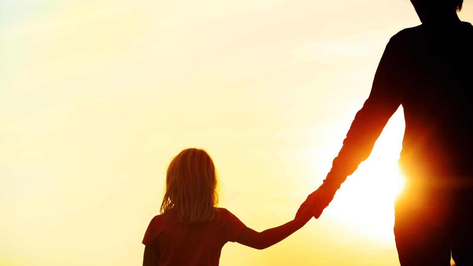 A silhouette of a father and daughter holding hands as the sun sets.