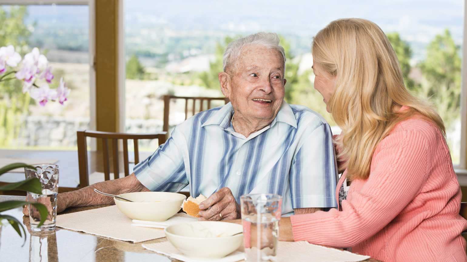 An older gentleman's daughter helps him eat soup at the table.