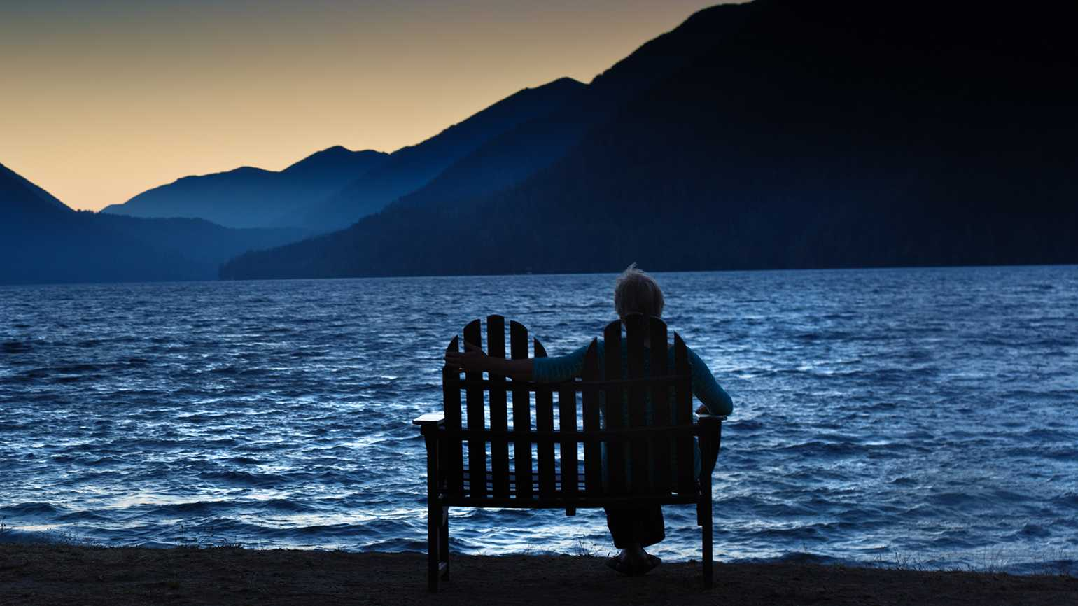 A mature woman watches the sun rise on a bench by a mountain lake