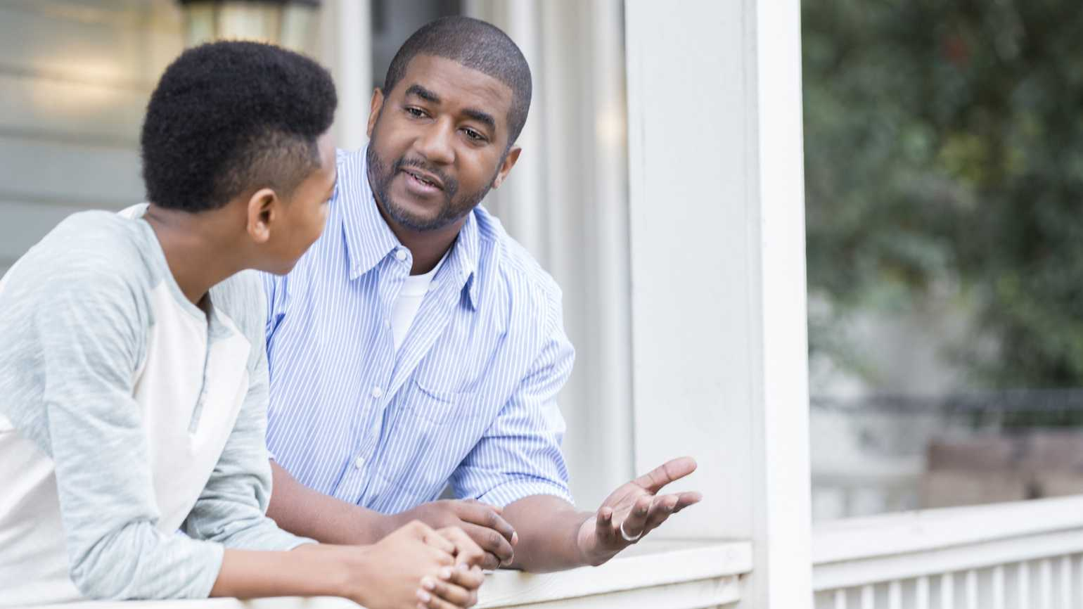 Father and son in serious front porch conversation.