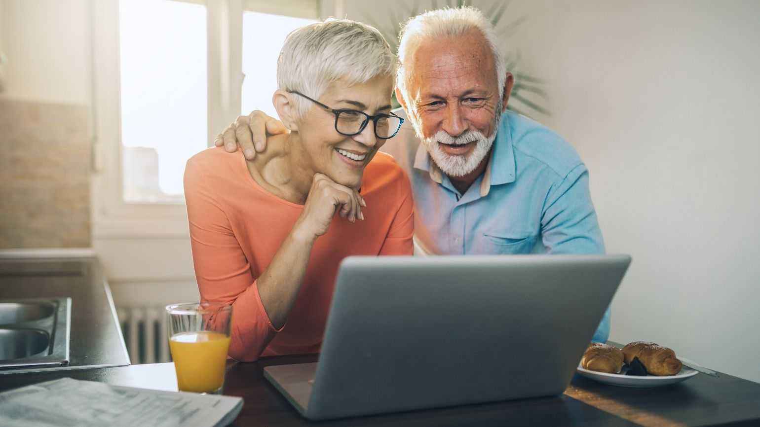 A man and woman video chat on a laptop