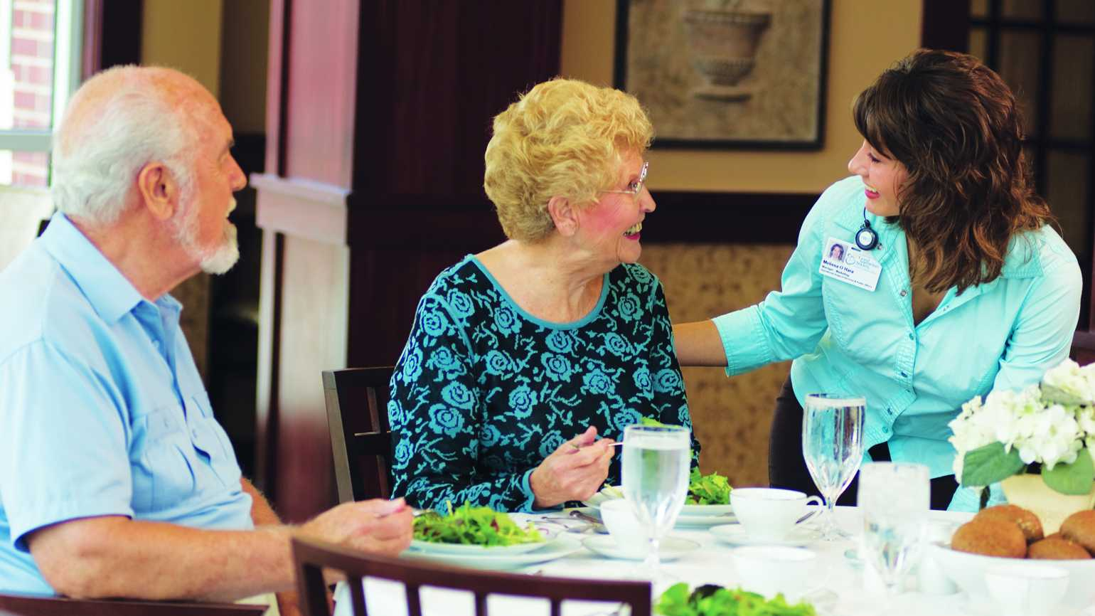 A senior citizen couple eating healthy at a table conversing with an aide.