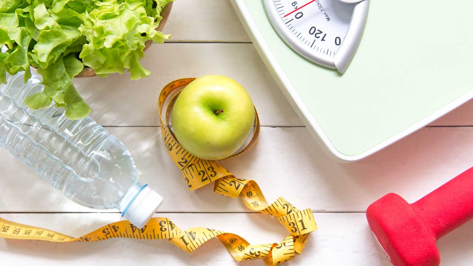Essential tools for weight loss such as a bottle of water, a scale, and a dumbbell
