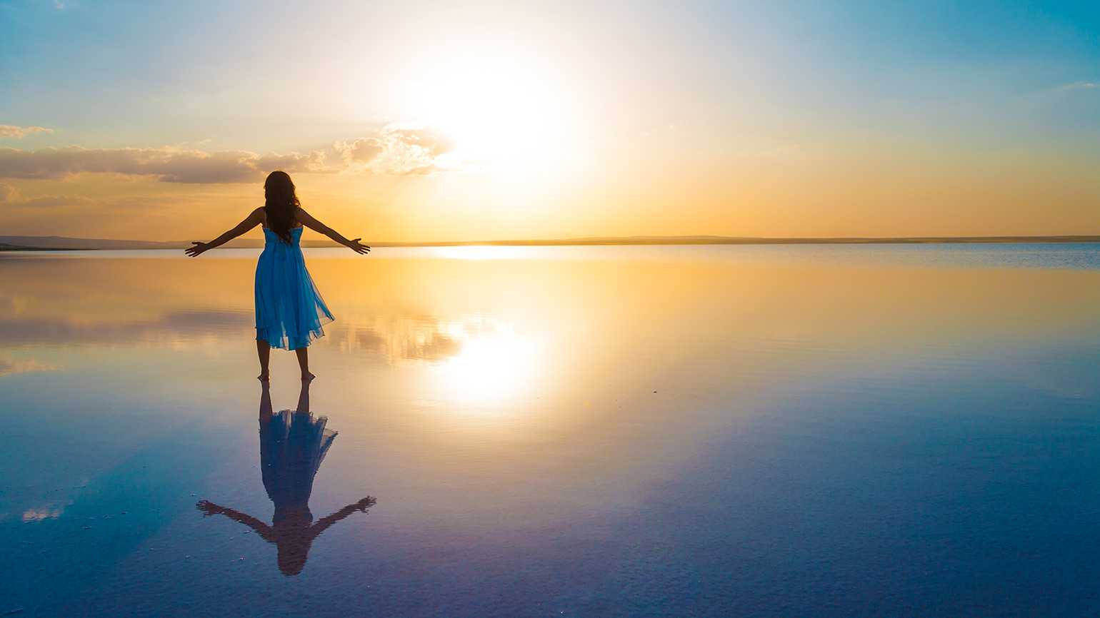 A woman stands at the edge of still water that reflects a sunrise