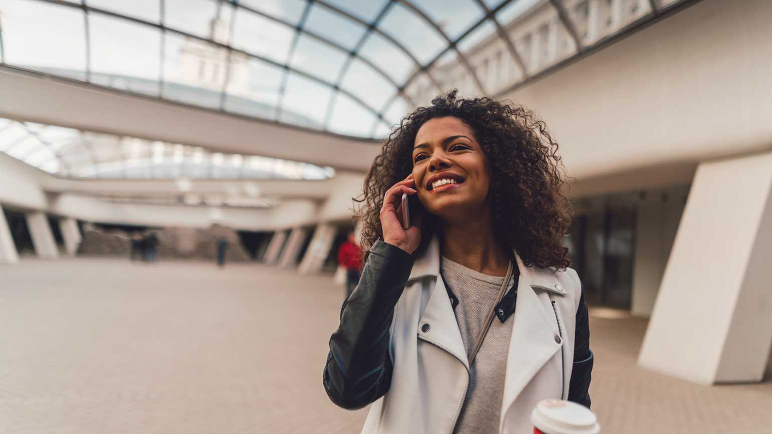 Mixed race woman enjoying a phone call in the subway station.