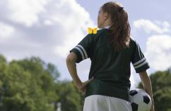 A young girl in a soccer uniform, with a yellow butterfly on her left shoulder