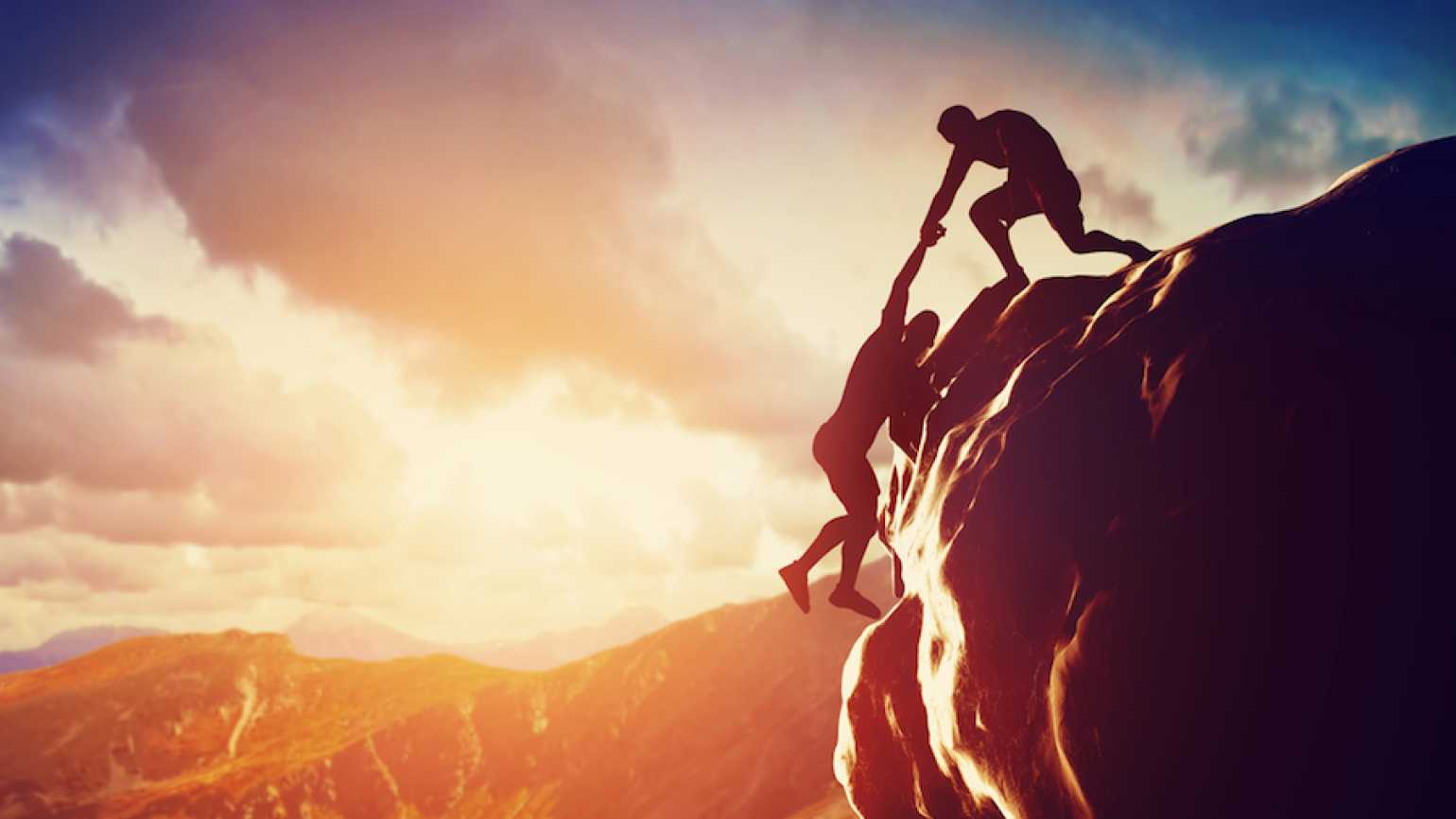 Man helping another man up a cliff. Shutterstock.