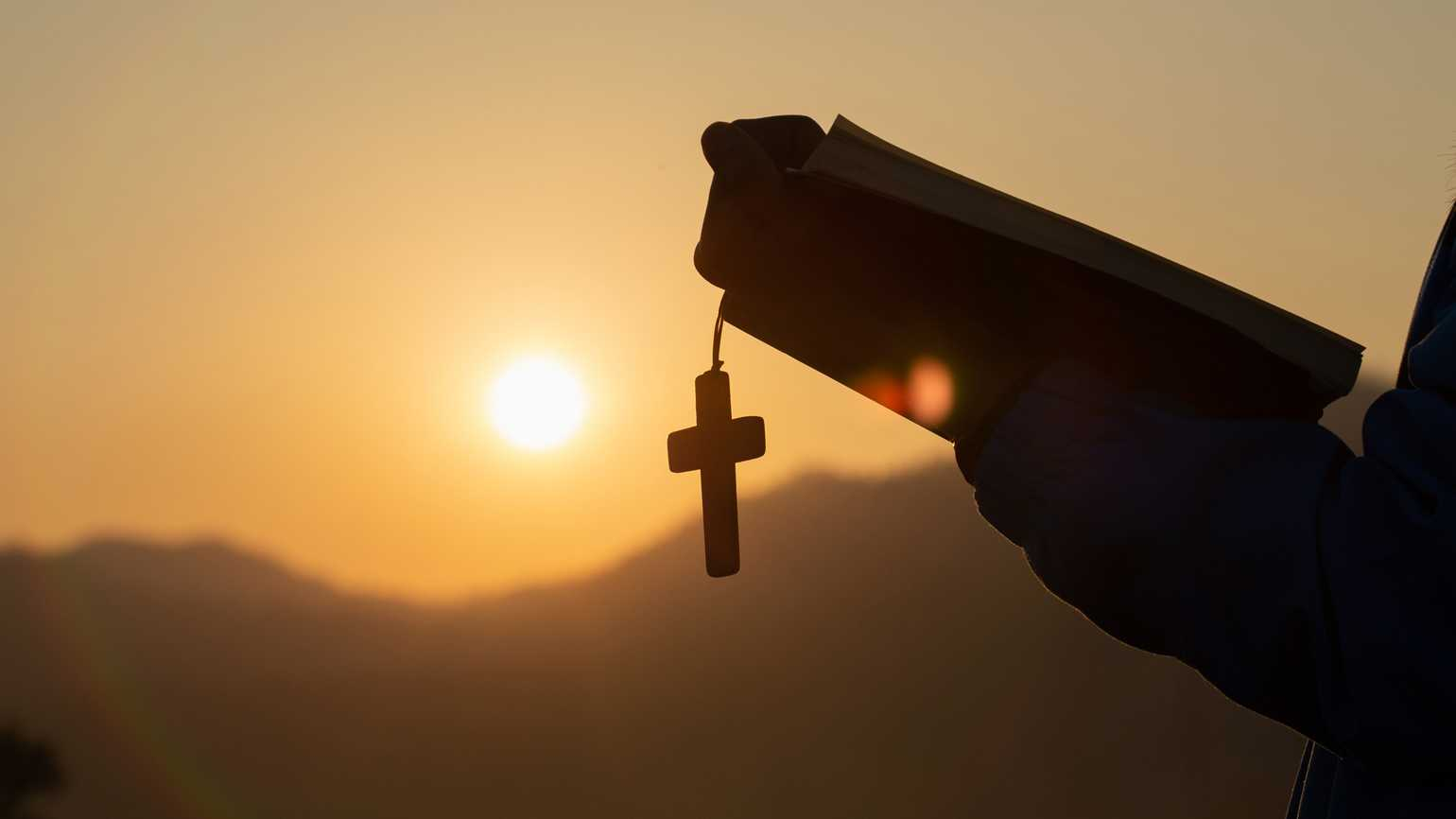 Silhouette of a person with a Bible and Holy Cross.