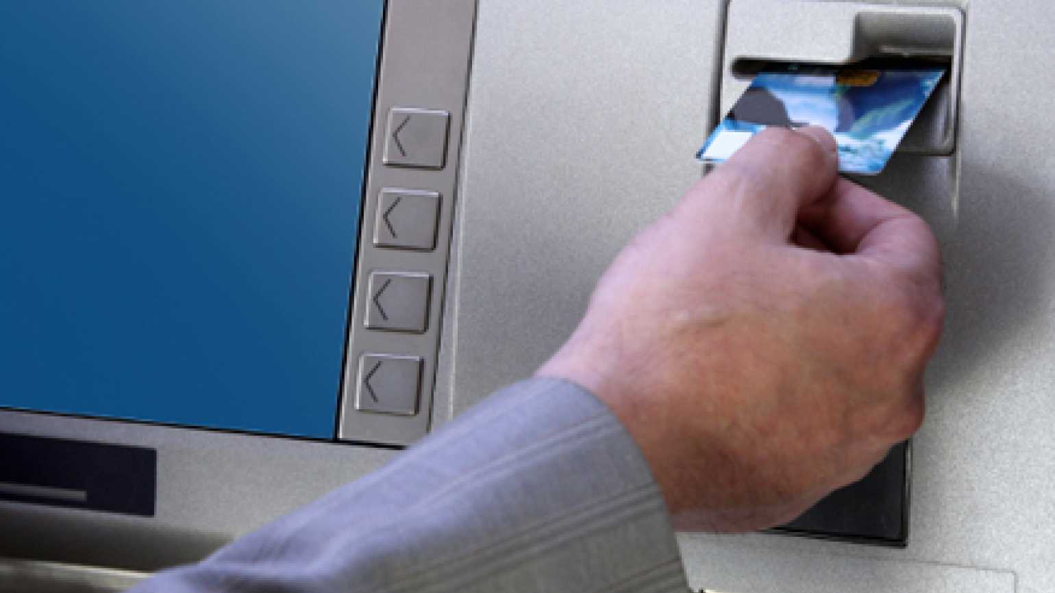A man inserts his bank card into an ATM