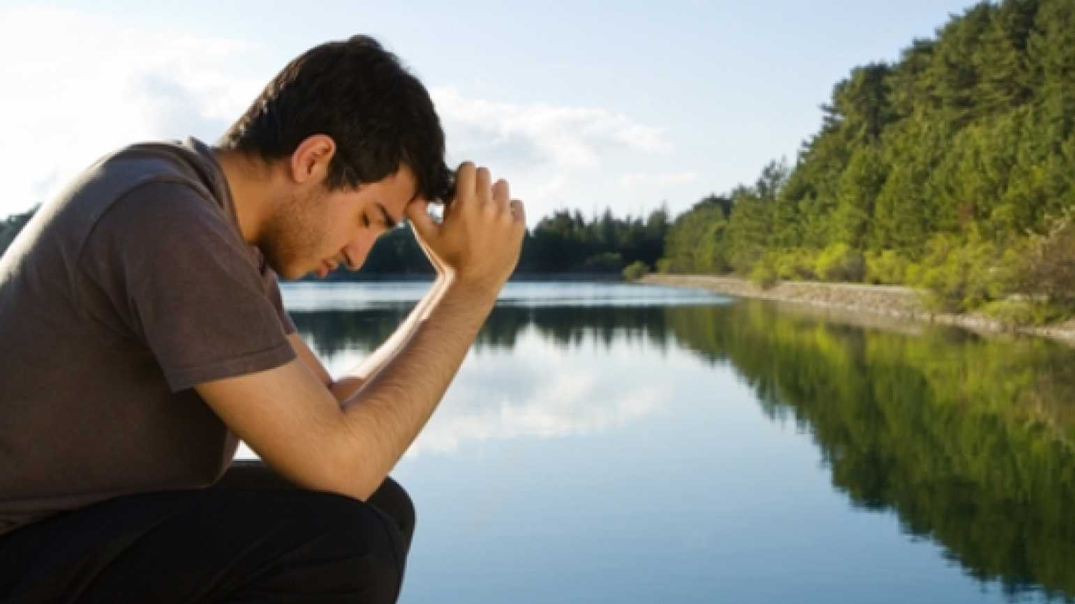 man praying in front of a lake with mountains behind him.