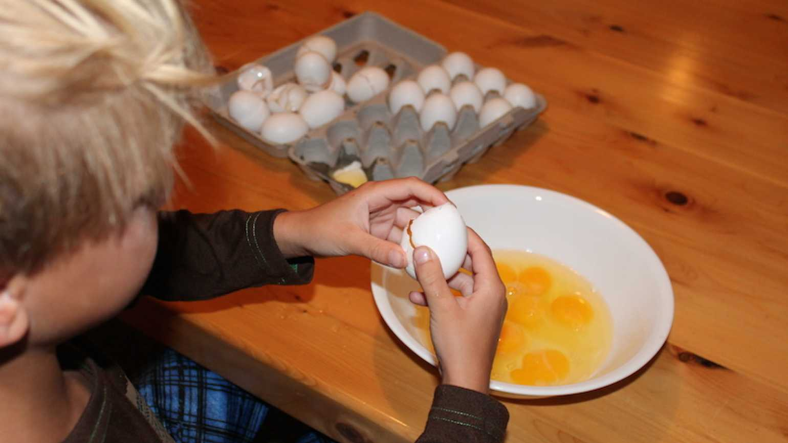 Shawnelle's son cracks eggs into a bowl.