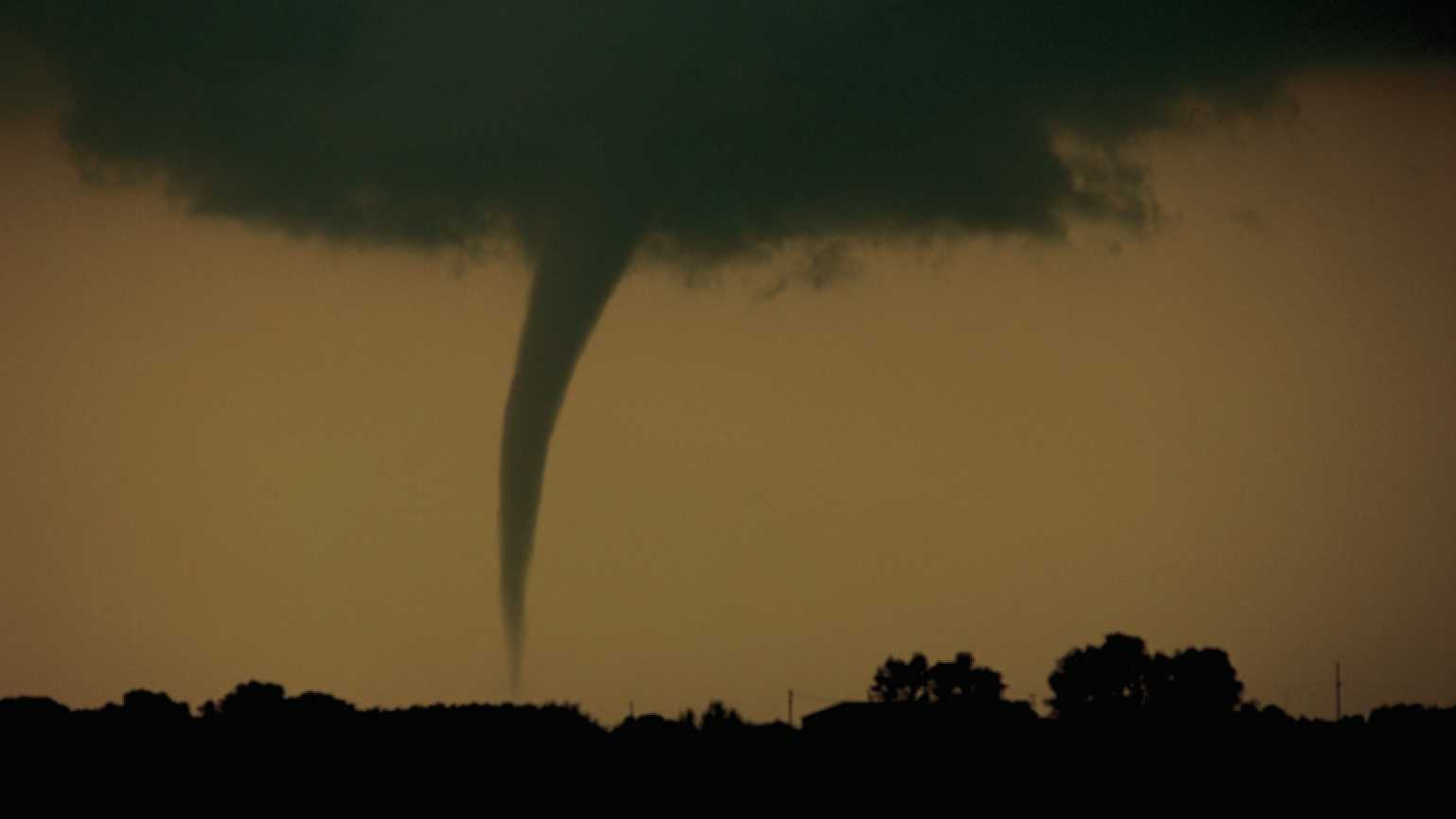 A funnel cloud dips down from dark, stormy clouds.
