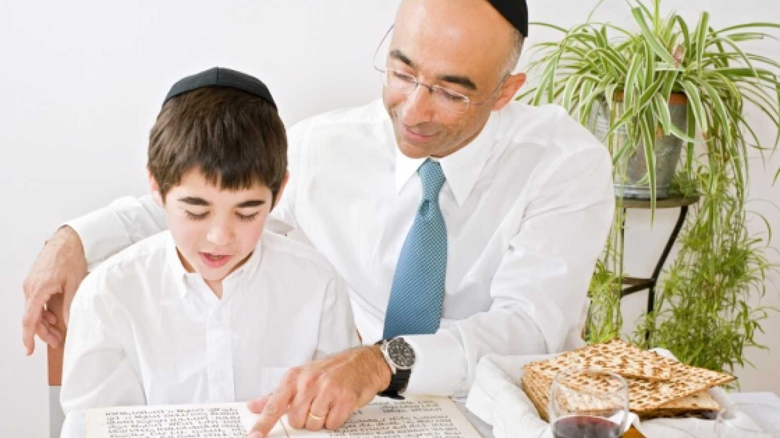 father and son celebrating Passover reading