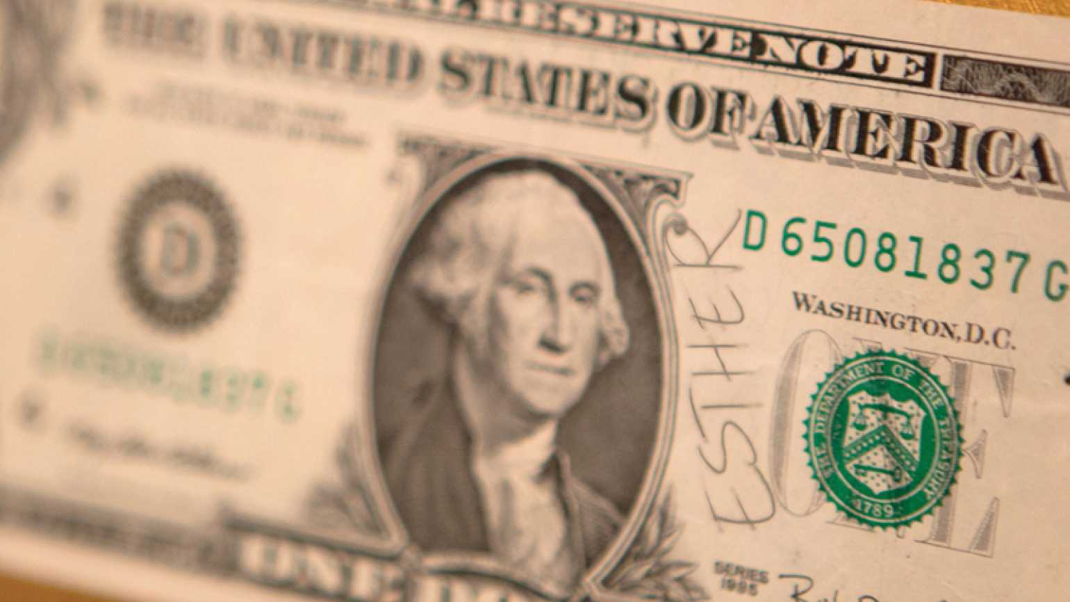 A dollar bill with the name Esther written on it.