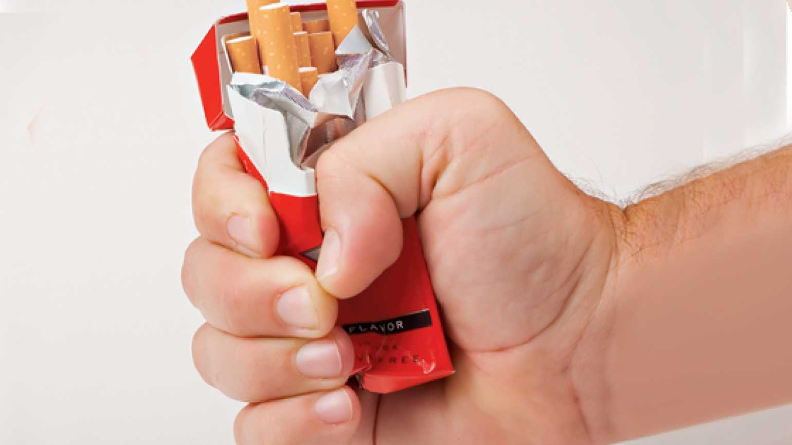 A man's hand crumples a pack of cigarettes.