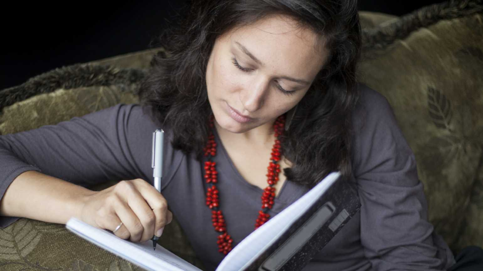 A woman writes in her journal.