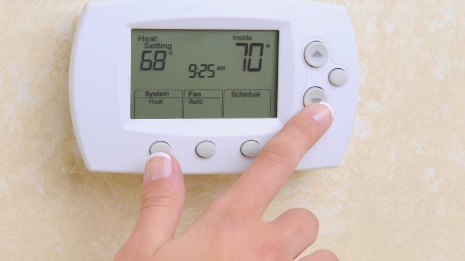 woman turning down the heat on thermostat