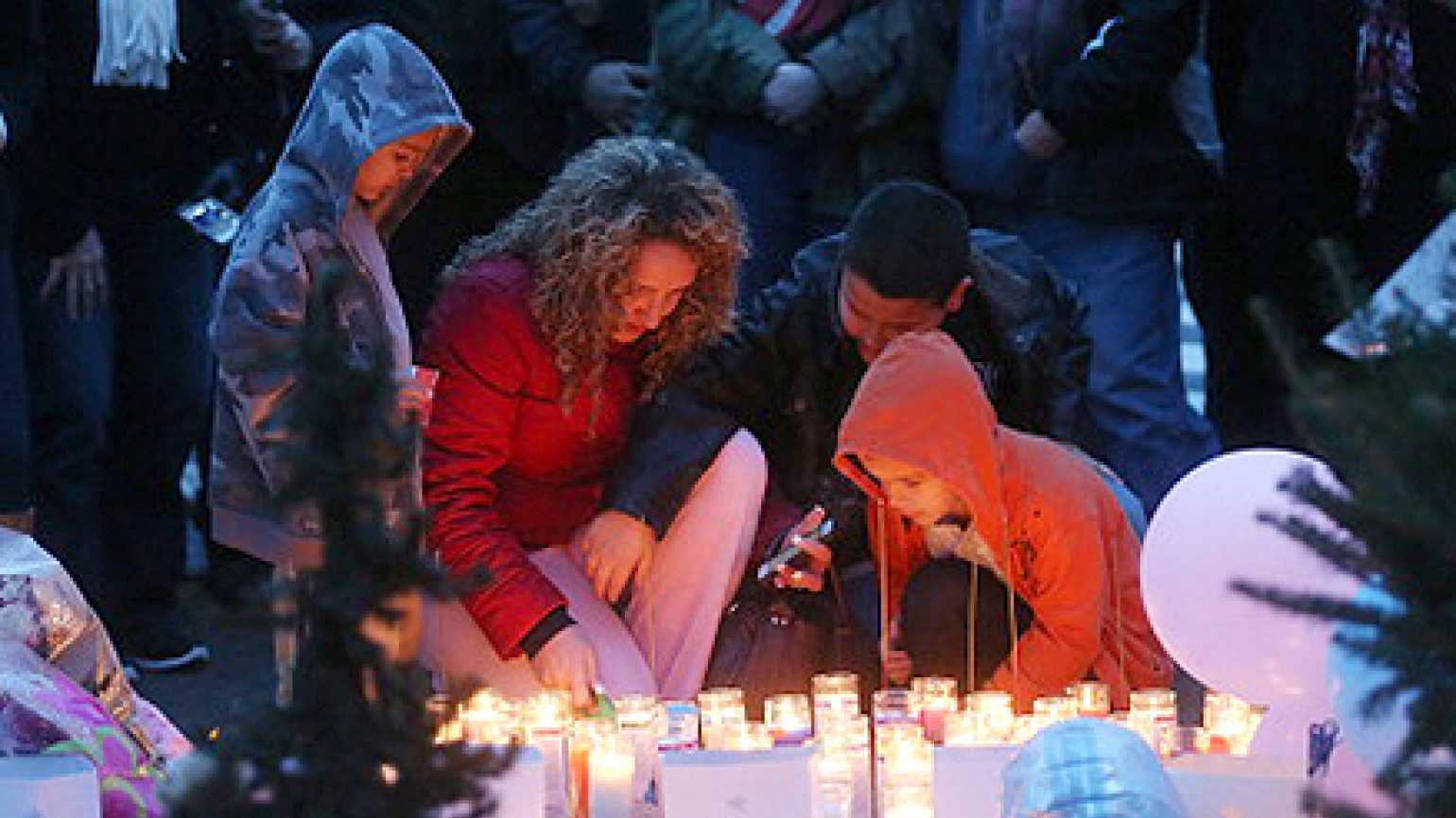 Mourners gather to pray and light candles in the darkness