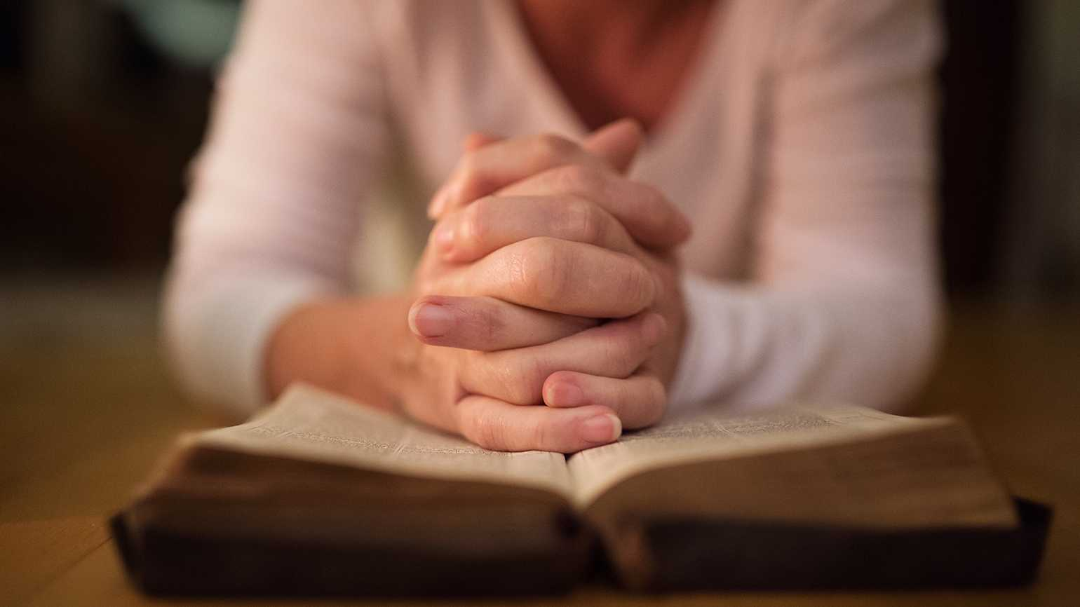 Woman's hands praying over a bible