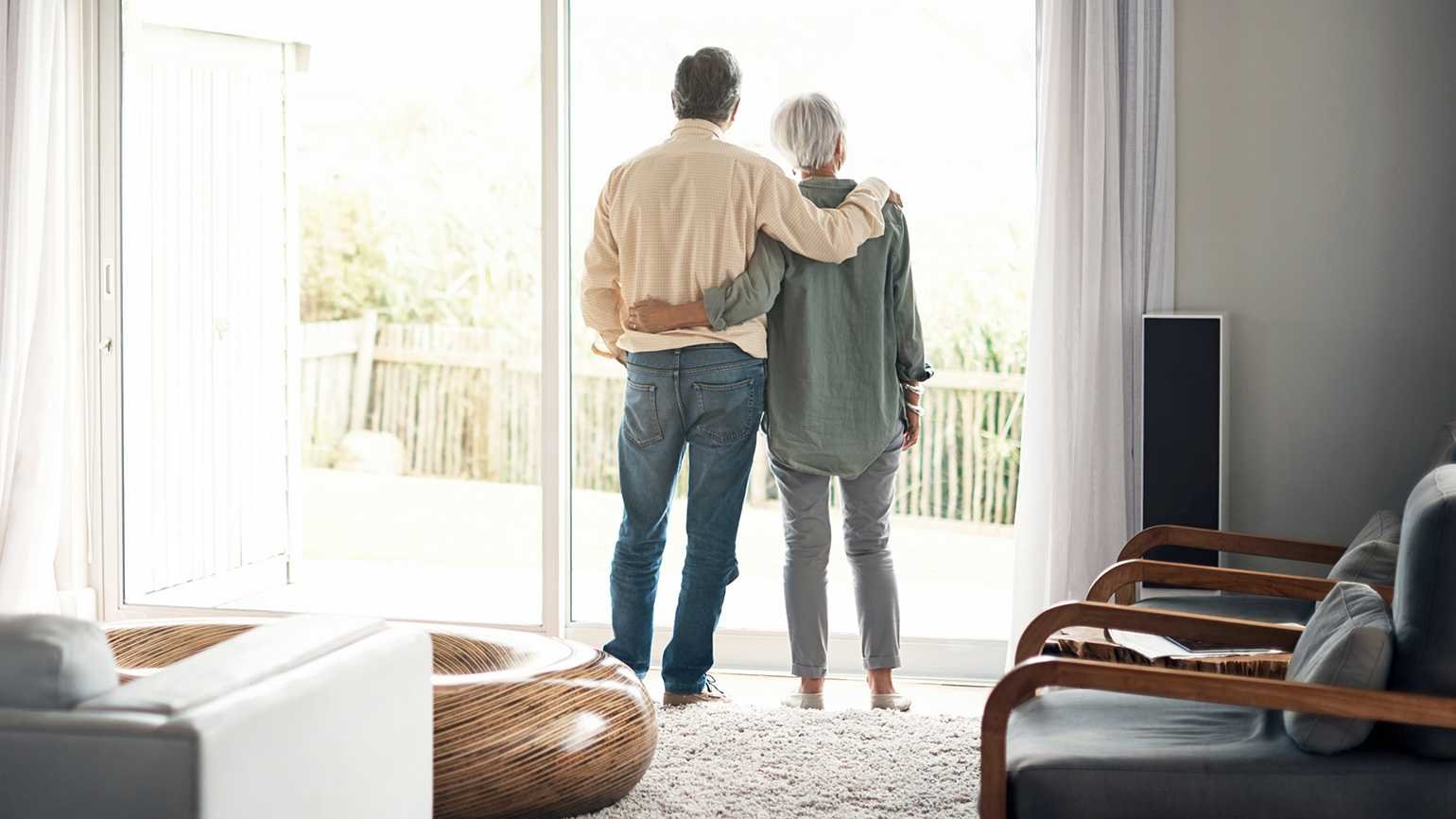 A husband/caregiver stands gazing out the window with his arm around his wife's shoulder
