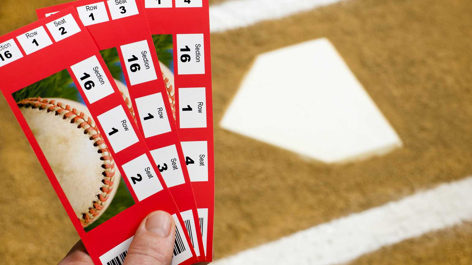 A Hand holding three baseball ticket stubs at home plate with the chalk lines of the batter's box