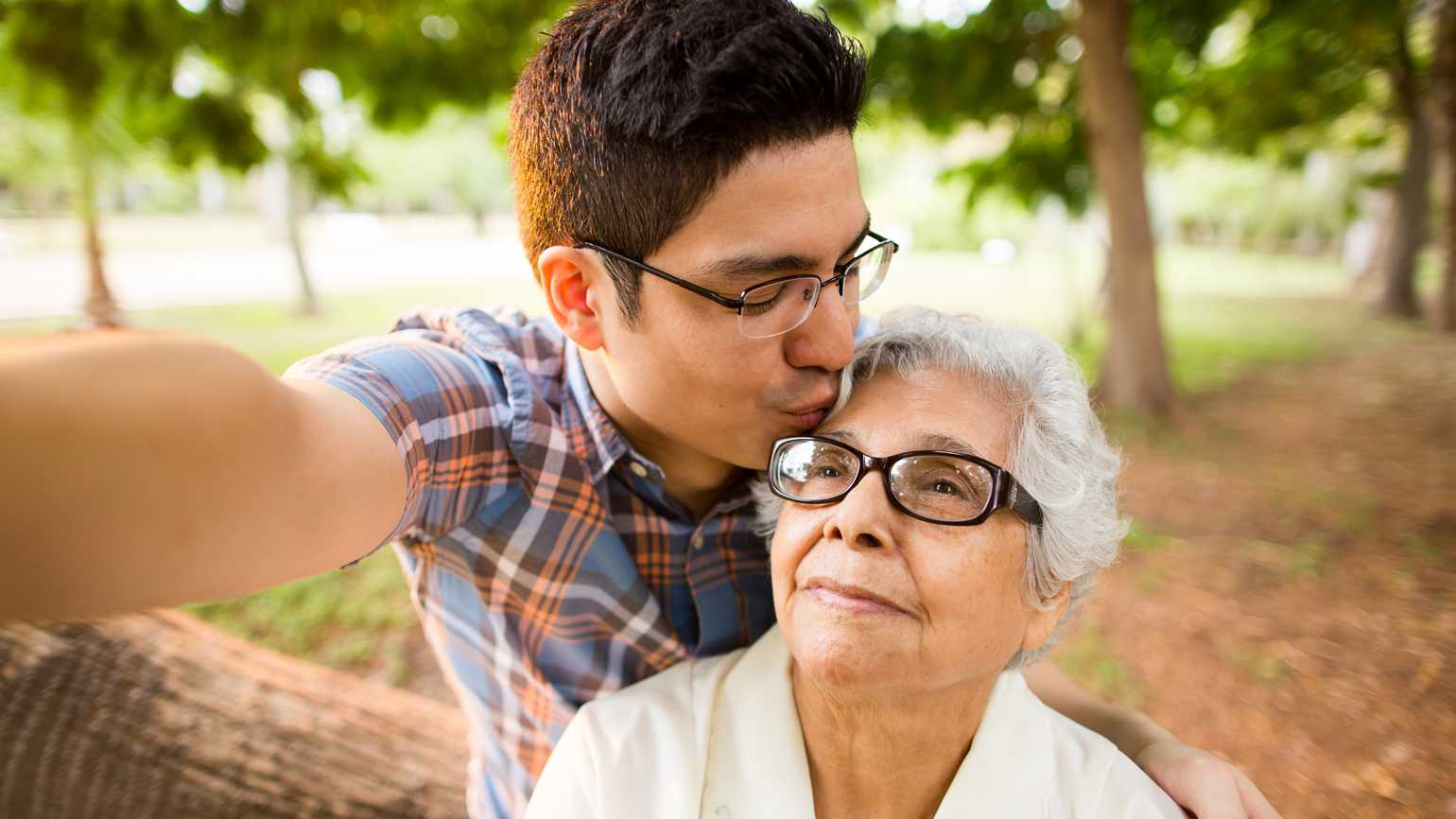 A millennial grandson showing affection to his grandmother.