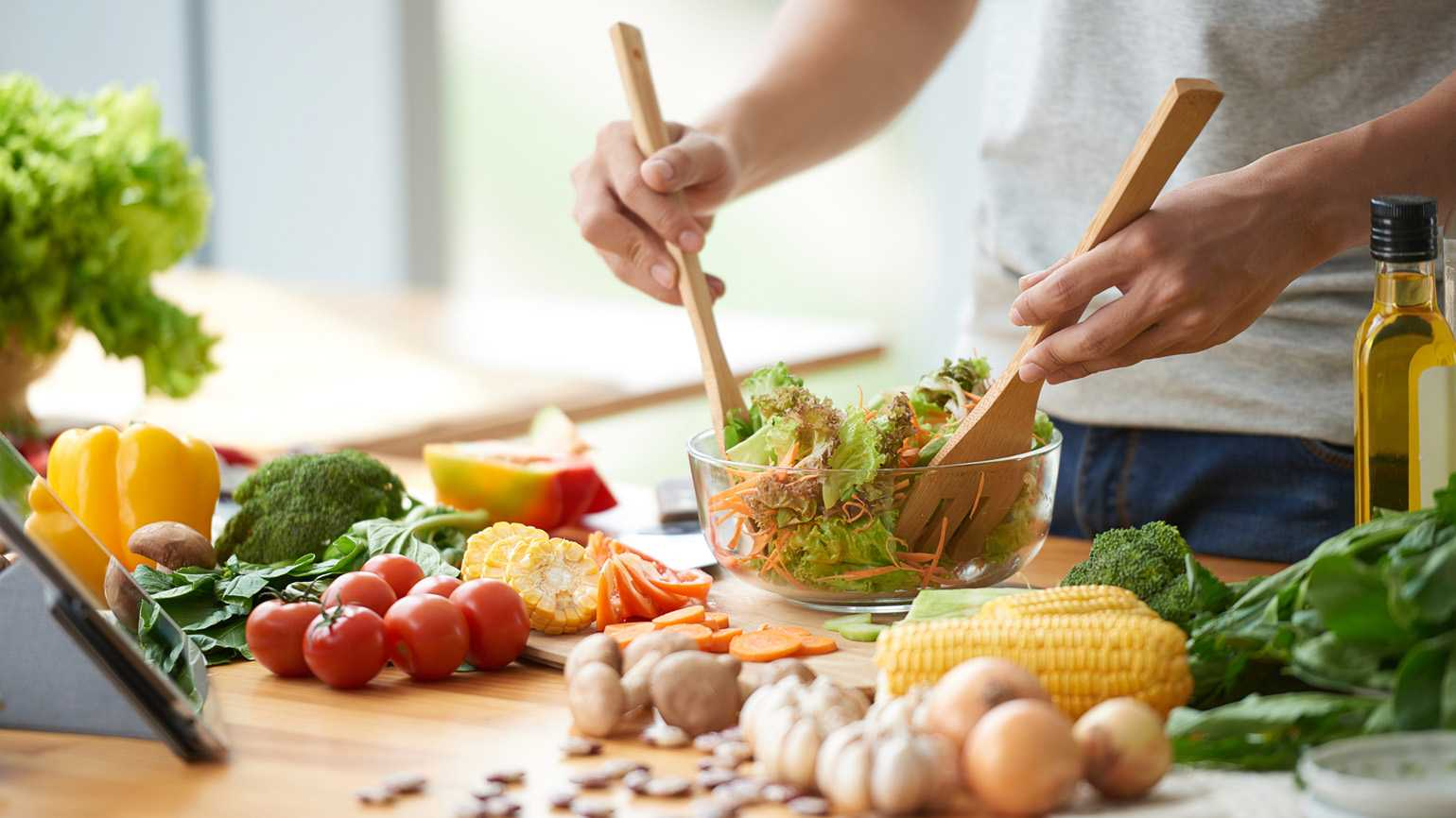 A caregiver tossing a healthy, nutritious salad in the kitchen.