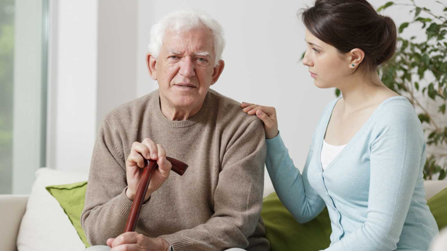 A young woman comforts an ailing older man in his home