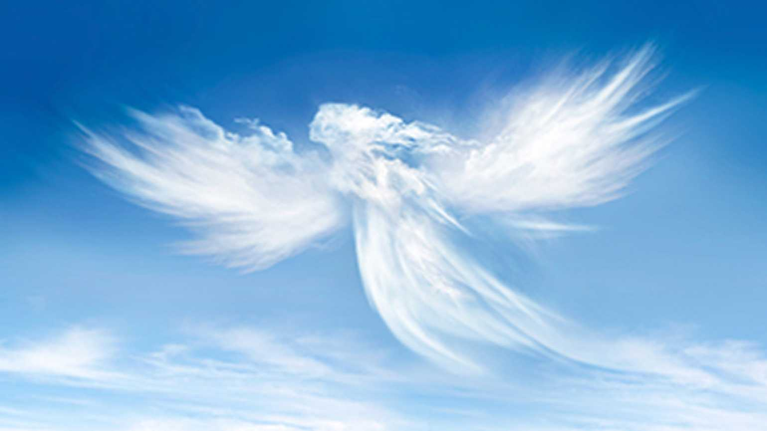 A cloud in the shape of an angel in a blue sky.