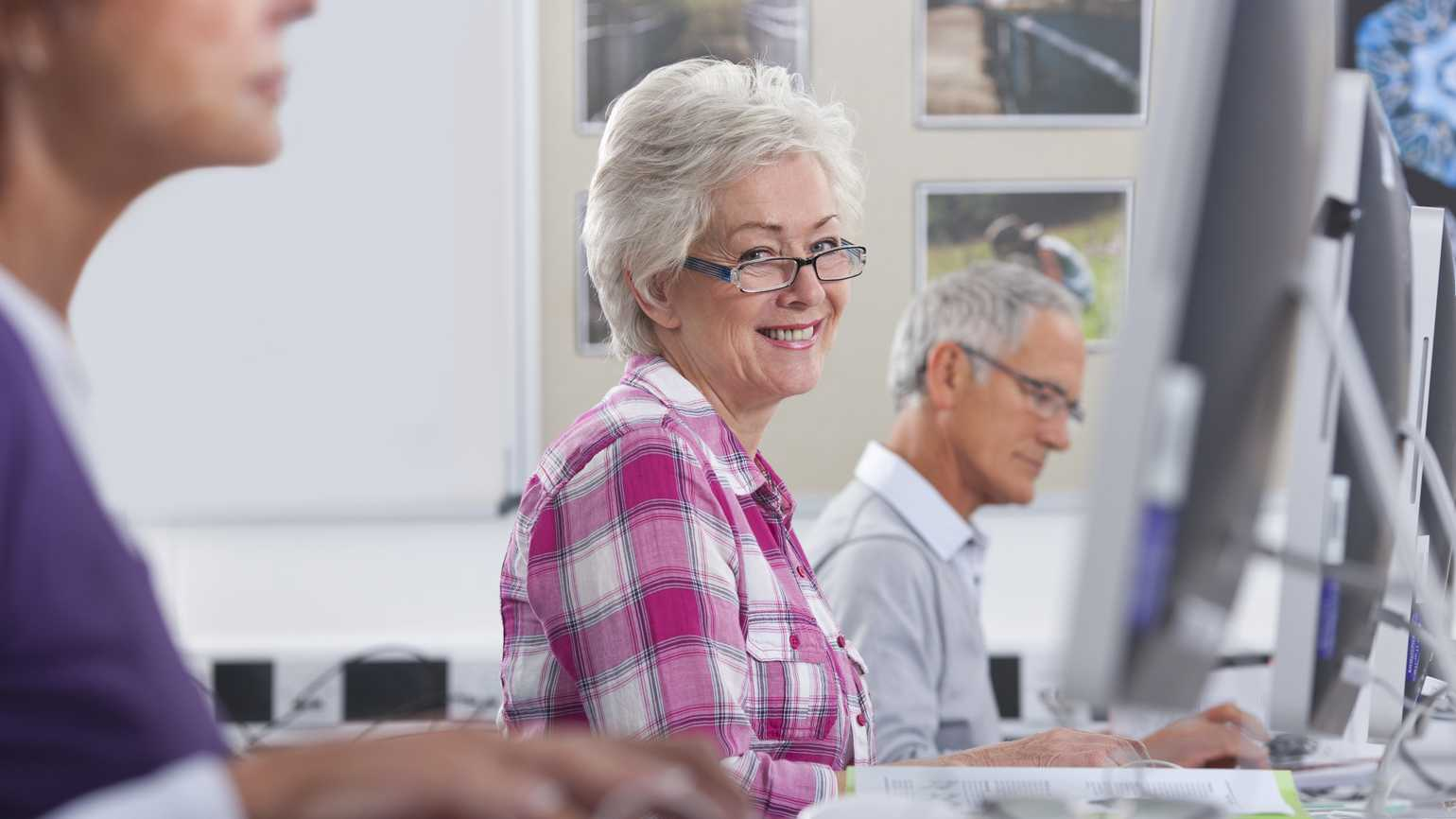 A smiling senior citizen woman learning how to use the Internet in a classroom.