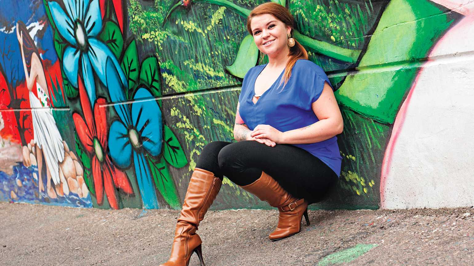 Lindsay Day-Walker sitting against a colorful mural on a brick wall.