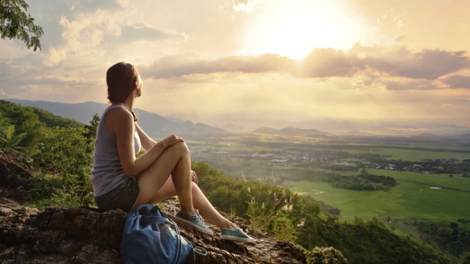 Woman enjoying the sunrise and living her life's dream.