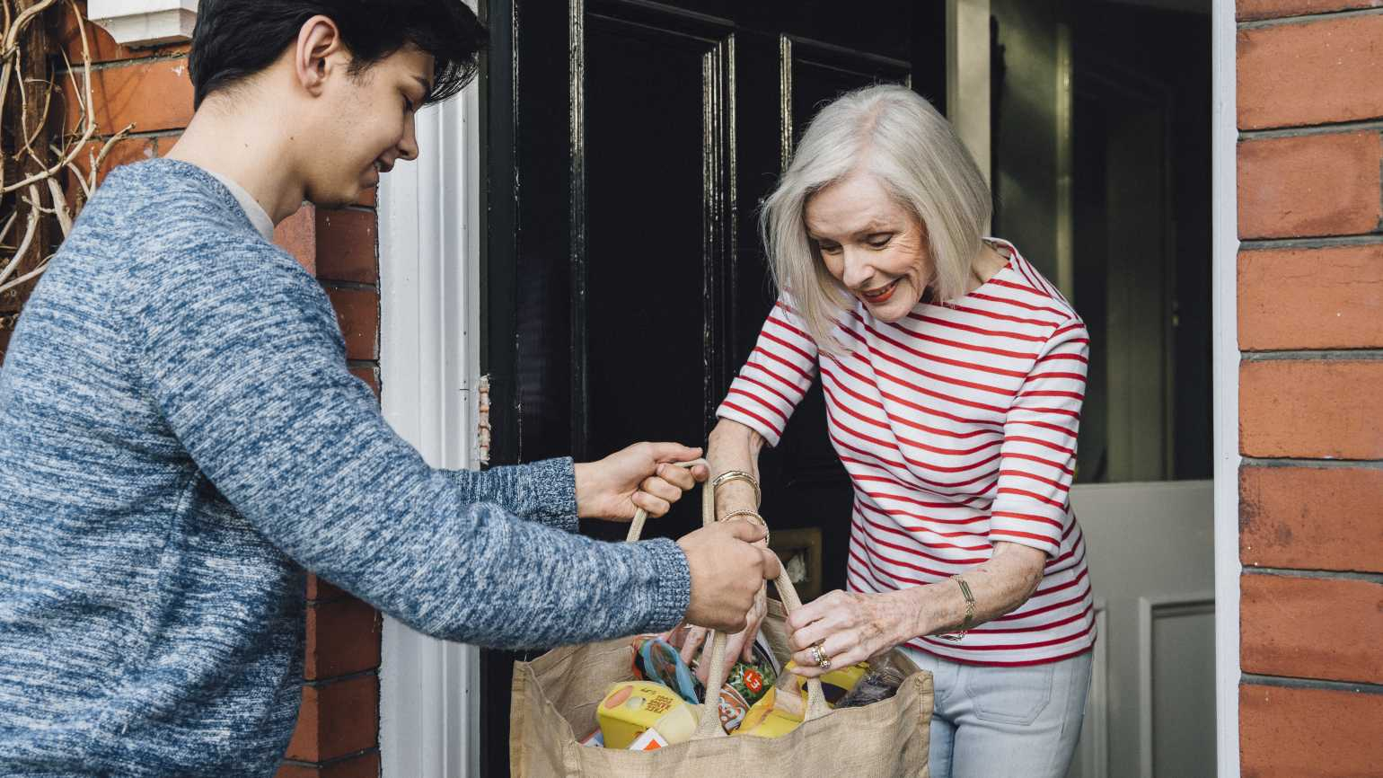 young boy helps older woman with bags, Getty Images