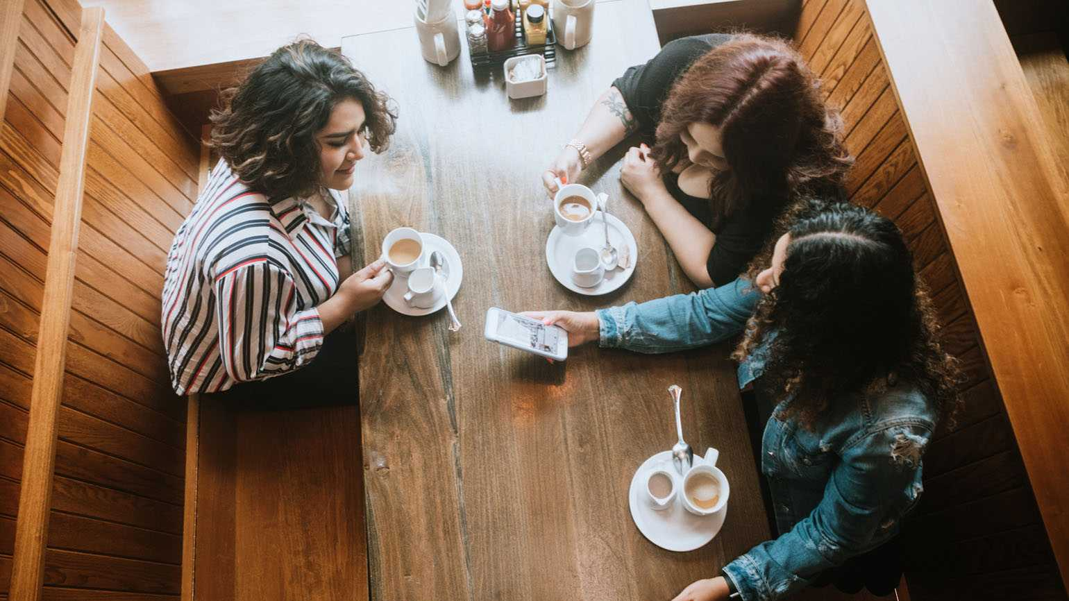 Three friends having coffee together in a cafe.