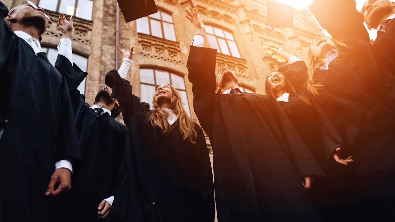 A group of graduates throwing their caps in the air.